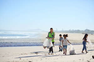 Children volunteers cleaning up beach litter