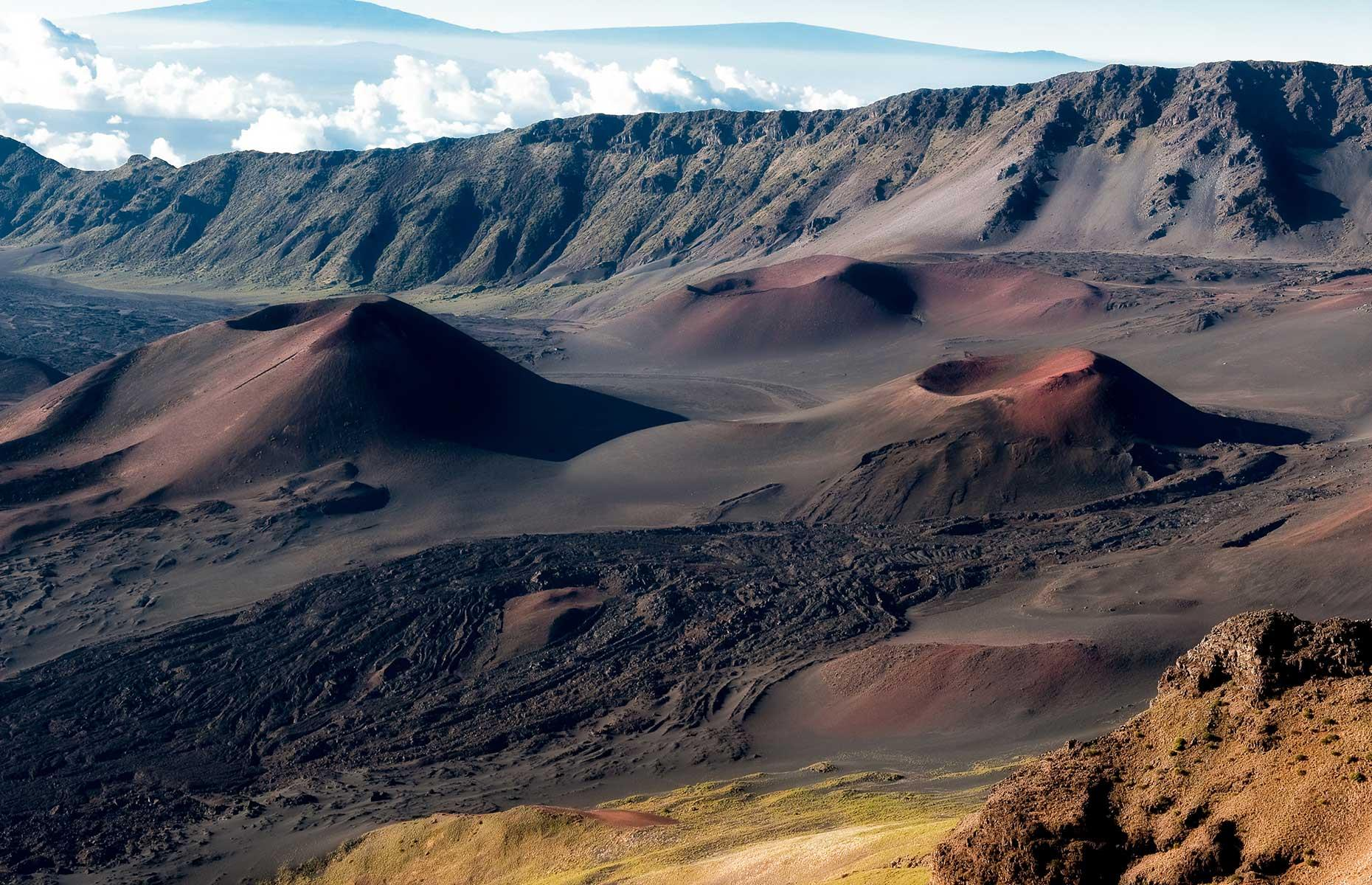 Slide 12 of 61: These Mars-like landscapes exist in the remote Summit District of Hawaii's Haleakalā National Park. Here, the namesake Haleakalā, a gargantuan shield volcano, reaches 10,023 feet (254.5m), and brave hikers come to spot native flora and fauna and experience some of the best stargazing in the state. Elsewhere in the park, the Kīpahulu District complements the Summit with its waterfalls, greenery and rugged coastline.