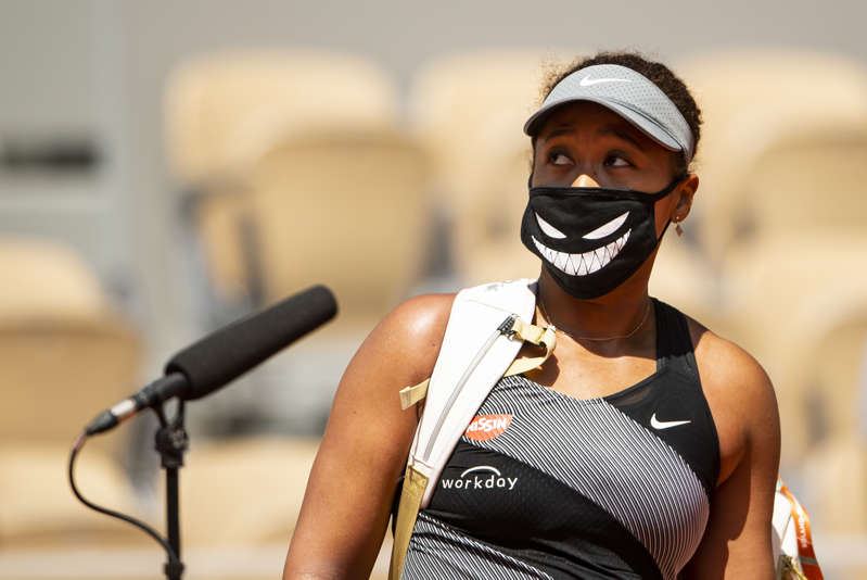 PARIS, FRANCE - MAY 30: Naomi Osaka of Japan is interviewed by Fabrice Santoro of France after her victory over Patricia Maria Țig of Romania in the first round of the women's singles at Roland Garros on May 30, 2021 in Paris, France.