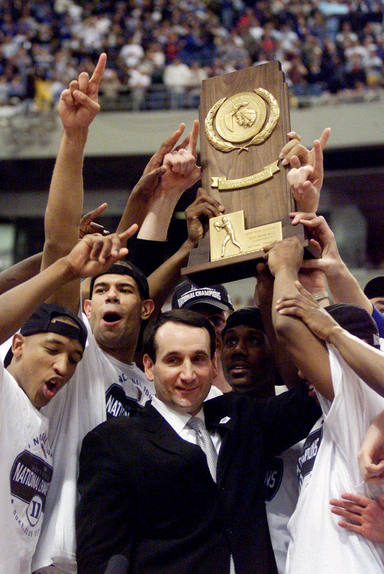 Shane Battier, Mike Krzyzewski standing in front of a crowd: Duke coach Mike Krzyzewski and his Blue Devils hoist the championship trophy after beating Arizona 82-72 in the championship game of the Final Four in Minneapolis on April 2, 2001.