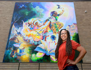Tia Richardson posing for the camera: Milwaukee mural artist Tia Richardson stands in front of one of her many Milwaukee-area murals, this one titled The Rebirthing of the Earth Mother she created in 2018 located at 2215 Vel R. Phillips Ave. in Milwaukee on Monday, May 31, 2021. Richardson typically involves community members in painting the murals she designs as a way to promote unity and healing.