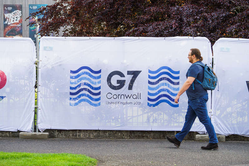 A member of the public walks passed G7 Summit signage erected outside the G7 media centre at the National Maritime Museum Cornwall, which is hosting the world's media for the upcoming G7 Summit, on May 29, 2021 in Falmouth, England. (Photo by Hugh R Hastings/Getty Images)