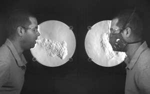 a man standing in front of a mirror posing for the camera: This image from the National Institute of Standards and Technology illustrates airflow when coughing with and without a mask. Credit: M. Staymates/N. Hanacek/NIST