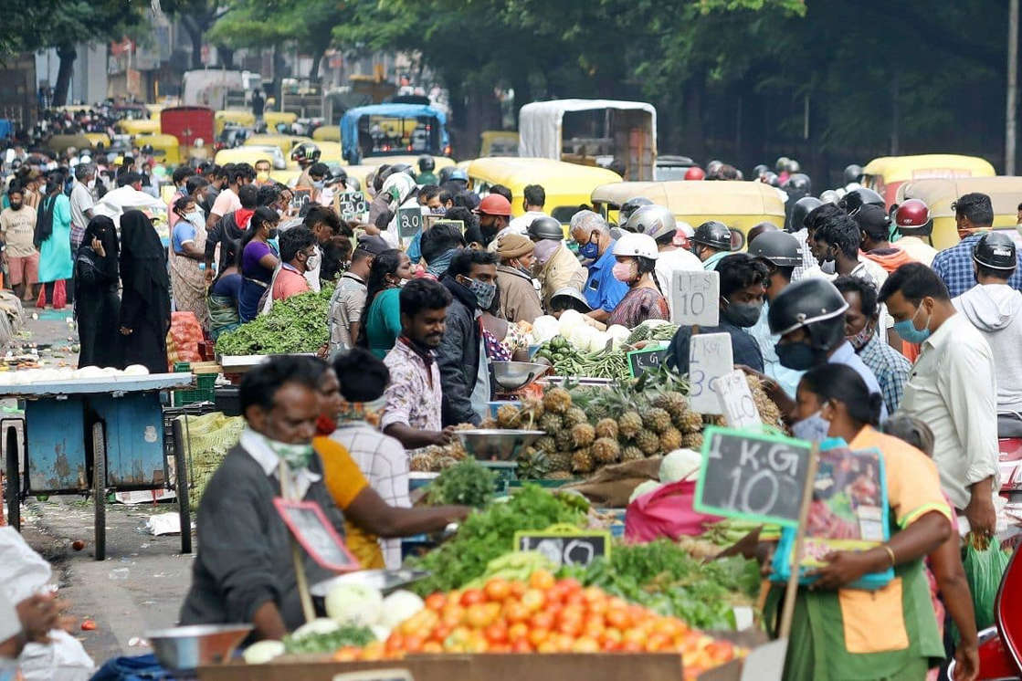 a group of people looking at a fruit stand: Massive crowding was seen at various markets in Delhi.