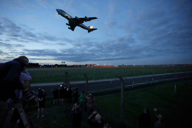 Slide 4 of 19: People watch Air Force One, carrying U.S. President Joe Biden and first lady Jill Biden, take off from RAF Mildenhall, near Bury St. Edmunds, in eastern England, to go to Cornwall for the G7 summit, Wednesday, June 9, 2021