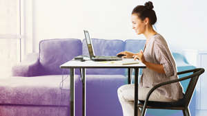 a person sitting on a chair in front of a laptop: AdobeStock