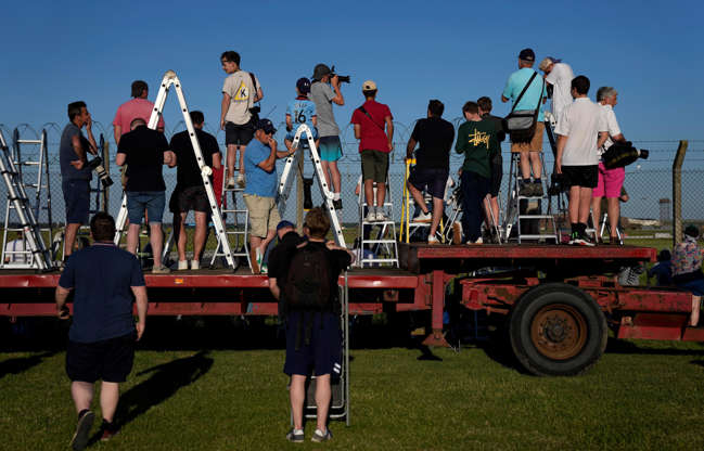 Slide 12 of 19: People stand atop stepladders to look over the fence as they wait for the arrival of U.S. President Joe Biden and first lady Jill Biden in Air Force One at RAF Mildenhall, near Bury St Edmunds, in eastern England, Wednesday, June 9, 2021.