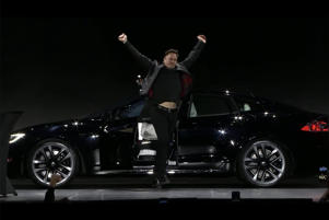 a man riding a motorcycle in front of a car: The Model S will shift itself and this man is excited about it. Tesla