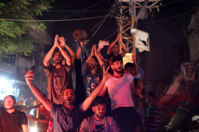 Palestinians celebrate in the streets following a ceasefire, in Gaza City May 21, 2021. REUTERS/Mohammed Salem