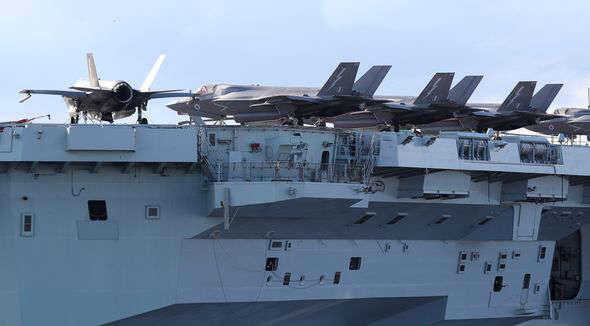 a large ship in the background: British fires missiles from HMS Queen Elizabeth