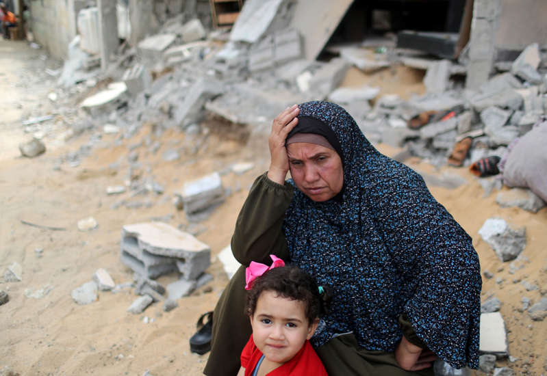 A Palestinian woman puts her hand on her head after returning to her destroyed house following Israel- Hamas truce, in Beit Hanoun in the northern Gaza Strip, May 21, 2021. REUTERS/Mohammed Salem