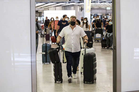 a group of people standing around a bag of luggage: Green list expanding soon: Traveller