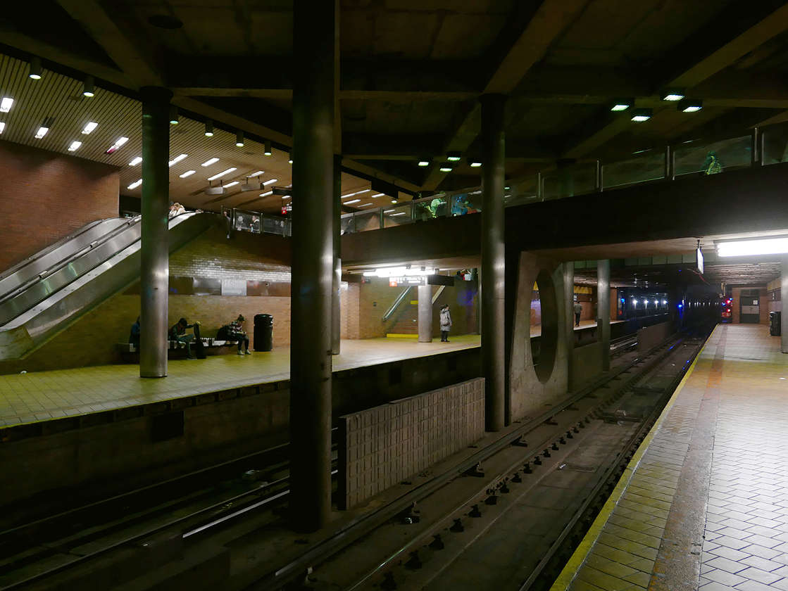 a subway train at a train station: Bystanders pulled the man out of the track area before the next train arrived