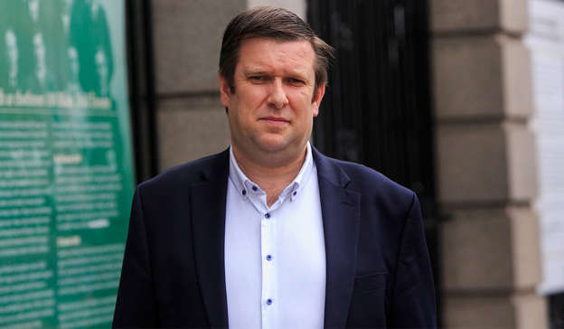 a man wearing a suit and tie standing in front of a building: Adrian Cummins, chief executive of the Restaurants Association of Ireland (RAI), had a concise summary of the situation, tweeting: 'Fully vaccinated!! Goal Posts are changing.' Pic: Gareth Chaney/Collins Photos