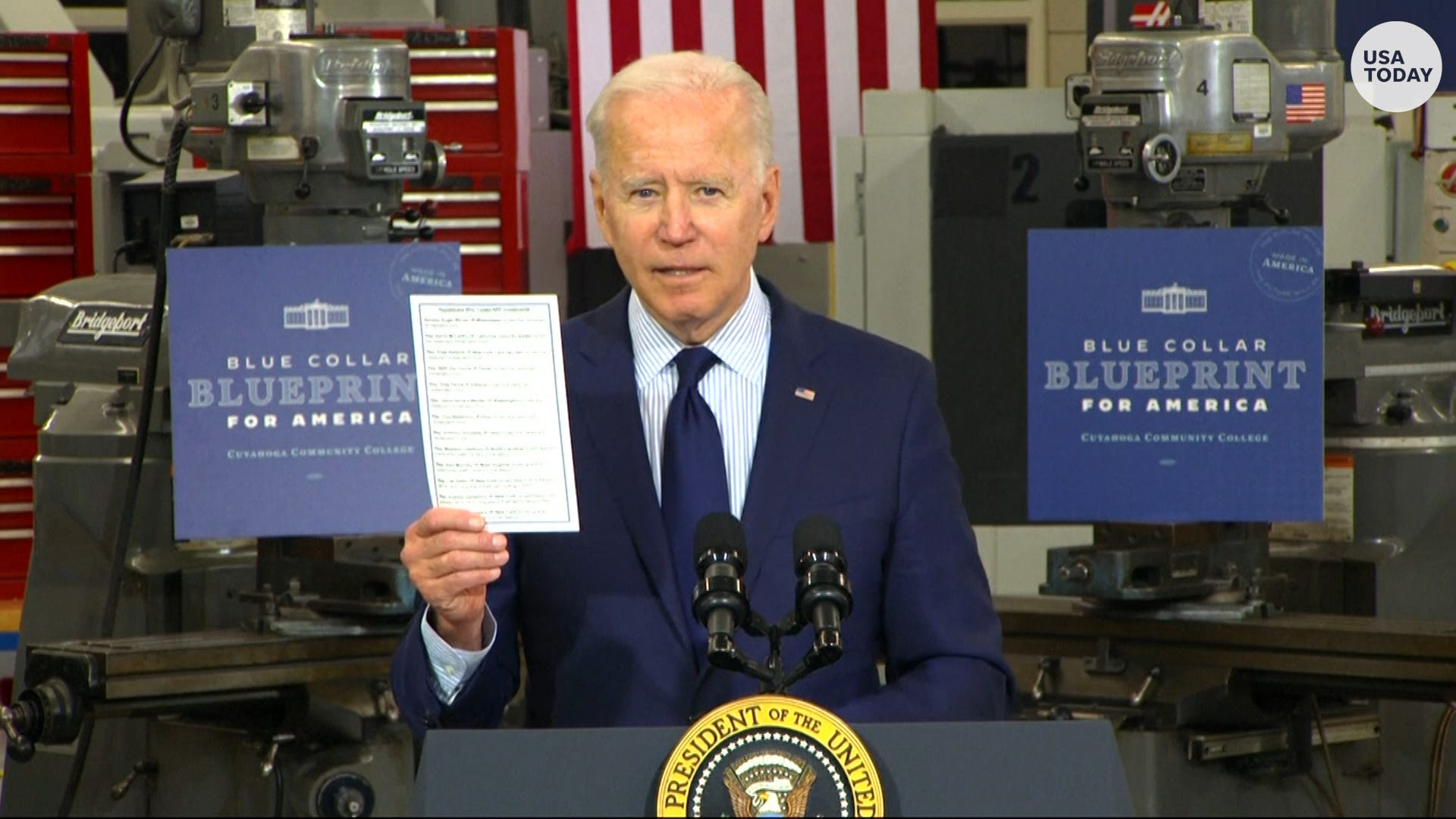 Joe Biden in a suit standing in front of a computer: President Joe Biden discussed his the economy, jobs and infrastructure during remarks in Cleveland.