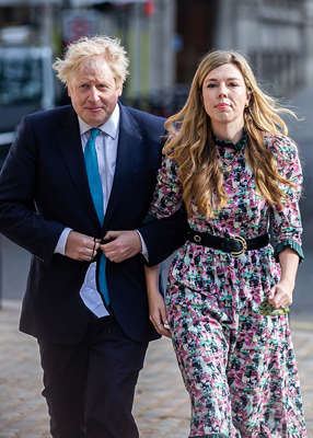 Boris Johnson wearing a suit and tie standing next to a woman: The parents welcomed Wilfred Lawrie Nicholas Johnson in the early morning of April 29, 2020 — shortly after Johnson was in hospital battling COVID. Pic: Tejas Sandhu/MI News/NurPhoto via Getty Images