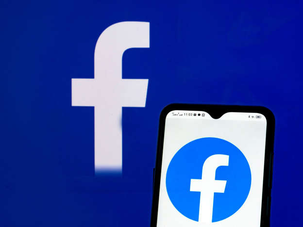 In this photo illustration Facebook, Inc. logo seen displayed on a smartphone and in the background.