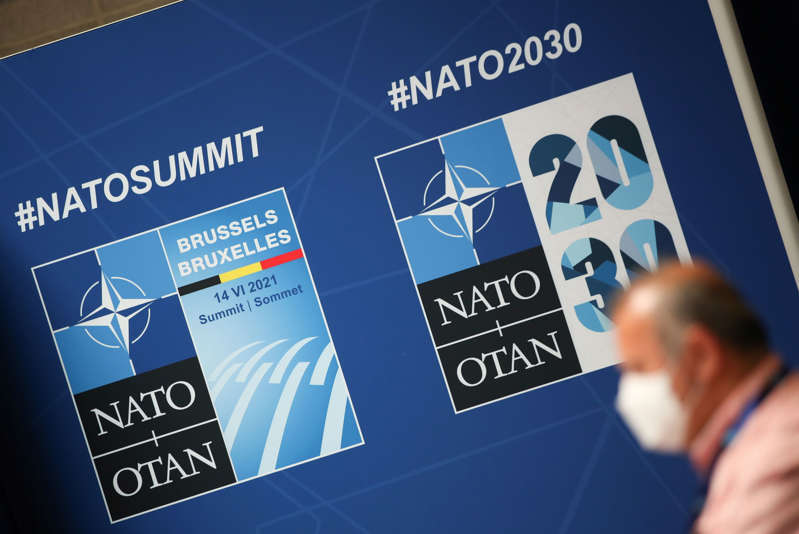 A person walks past posters ahead of a NATO summit, at the press centre in Brussels, Belgium, June 13, 2021. REUTERS/Yves Herman