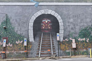 """a sign in front of a brick building: A 2014 mural titled """"Here's Your Train,"""" painted by Poconos artist Sean Turrell, as seen on a wall of a building in Stroudsburg on Thursday, June 10, 2021."""