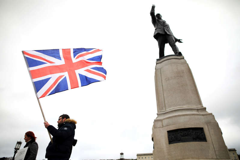 Loyalist protesters opposed to the Northern Ireland Protocol on Brexit make their point under the statue of former Unionist leader Lord Edward Carson at parliament buildings, Stormont, Belfast, Northern Ireland, Thursday, April 8, 2021 . (AP Photo/Peter Morrison)