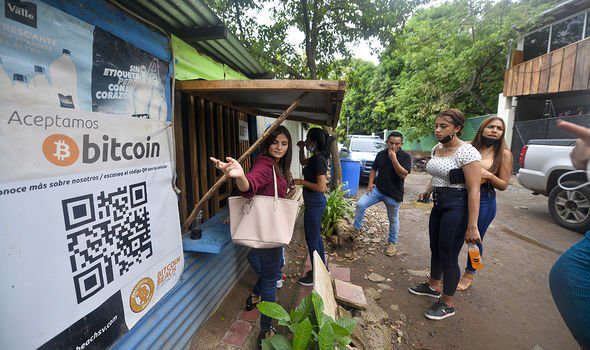 a group of people holding a sign: Bitcoin