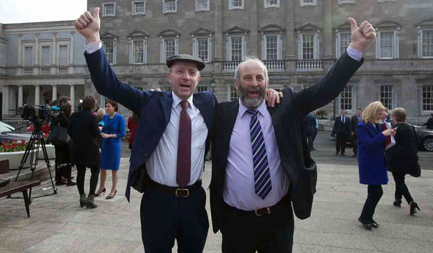 a group of people standing in front of a building: 'Well there's no one ringing you anyway, you do nothing for no one,' Michael Healy-Rae (left) responded, before saying all he could hear is 'yapping'. Pic: gareth chaney Collins