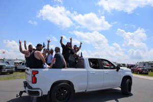 a group of people riding on the back of a truck: A group of NASCAR fans rides in a Chevy pickup on the campgrounds of Pocono Raceway in Long Pond, Pa.