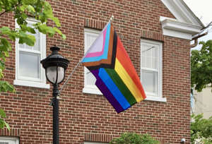 a sign in front of a brick building: A Progress Pride Flag flies outside Novus ACS in Courthouse Square in Stroudsburg. On Thursday, PennDOT announced that they will now permit citizens to self-confirm their non-binary gender designation on state-issued identification cards.