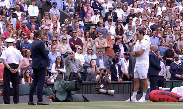 a group of people standing in front of a crowd: Roger Federer Wimbledon 2021