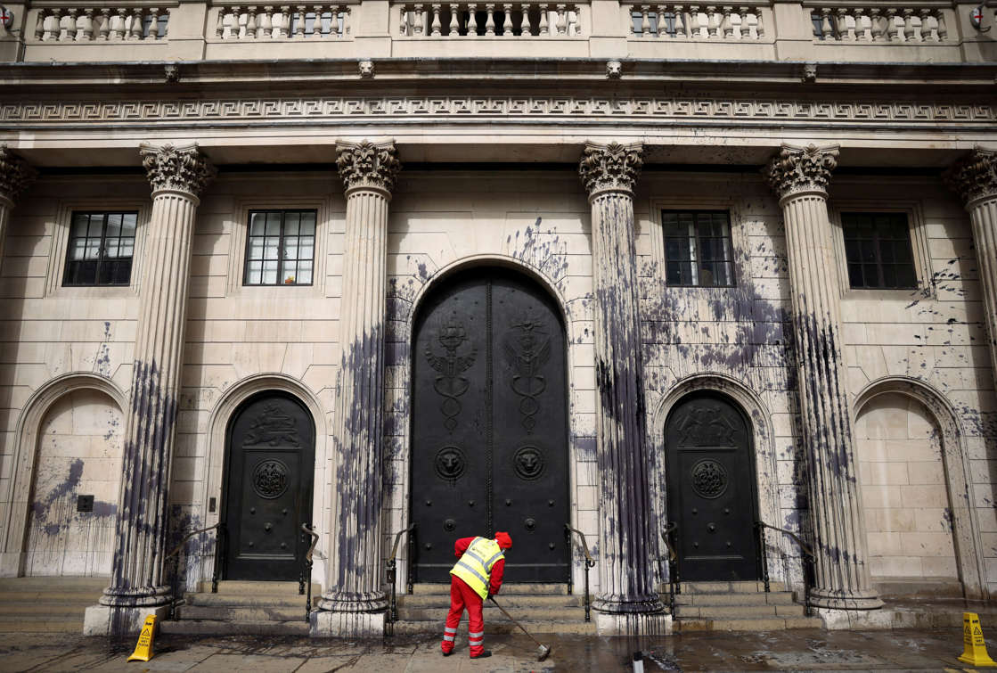 A council worker cleans up the floor in front of the Bank of England building which has been sprayed with black liquid during a protest by Extinction Rebellion activists, a global environmental movement, in London, Britain, April 1, 2021. REUTERS/Henry Nicholls     TPX IMAGES OF THE DAY