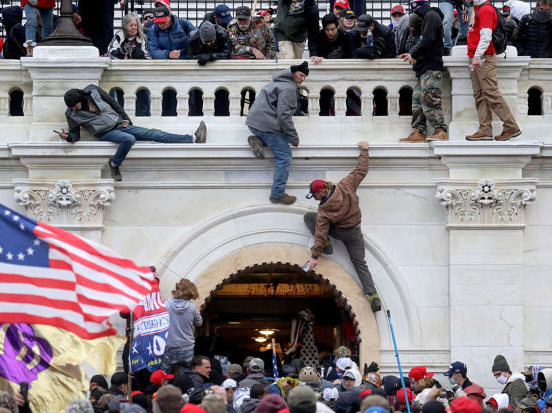 a crowd of people standing in front of a building: A mob of supporters of U.S. President Donald Trump fight with members of law enforcement at a door they broke open as they storm the U.S. Capitol Building in Washington, US 6 January 2021 - REUTERS