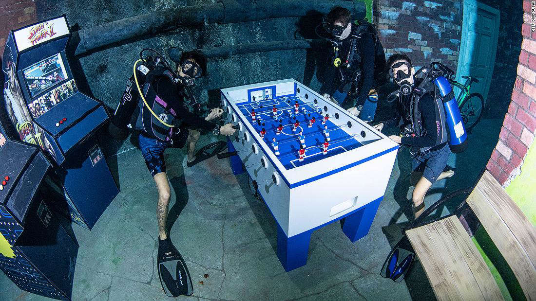 a group of people standing on top of a suitcase: Have you really played foosball if you've never played it underwater?