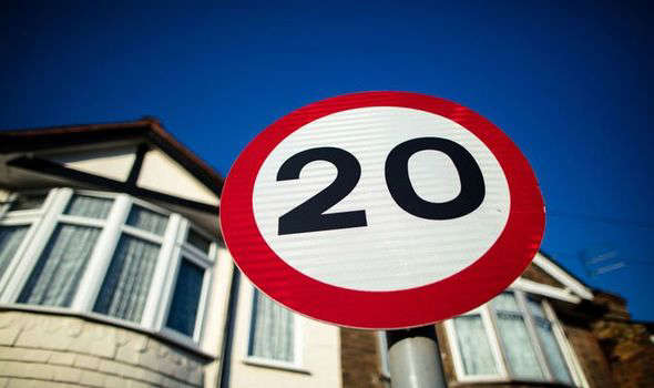 a sign on a pole in front of a building: new 20mph speed limit london