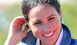 a close up of a person talking on a cell phone: MEGHAN MARKLE