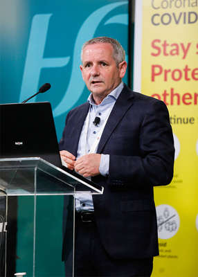 Paul Reid in a suit standing in front of a sign: When asked about 'John's' situation during an appearance on the same programme, HSE Chief Executive Paul Reid said he was 'sorry to hear that case'. Leon Farrell / Photocall Ireland