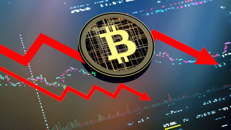 A bitcoin sits on a graph with red arrow going down