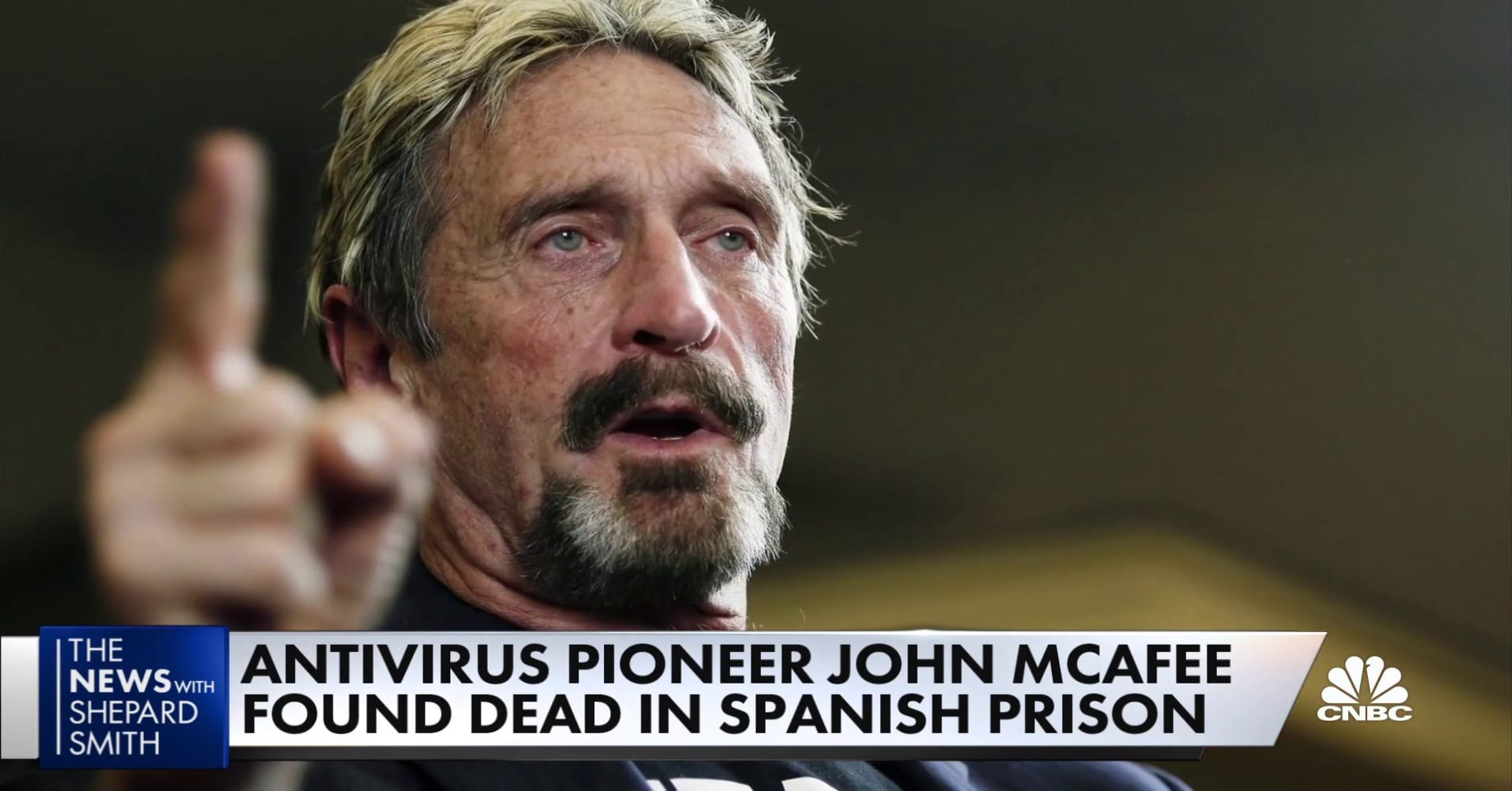 John McAfee with a beard looking at the camera: Antivirus pioneer John McAfee was found dead on Wednesday in his prison cell in Spain. He was 75 years old. His death is still being investigated.