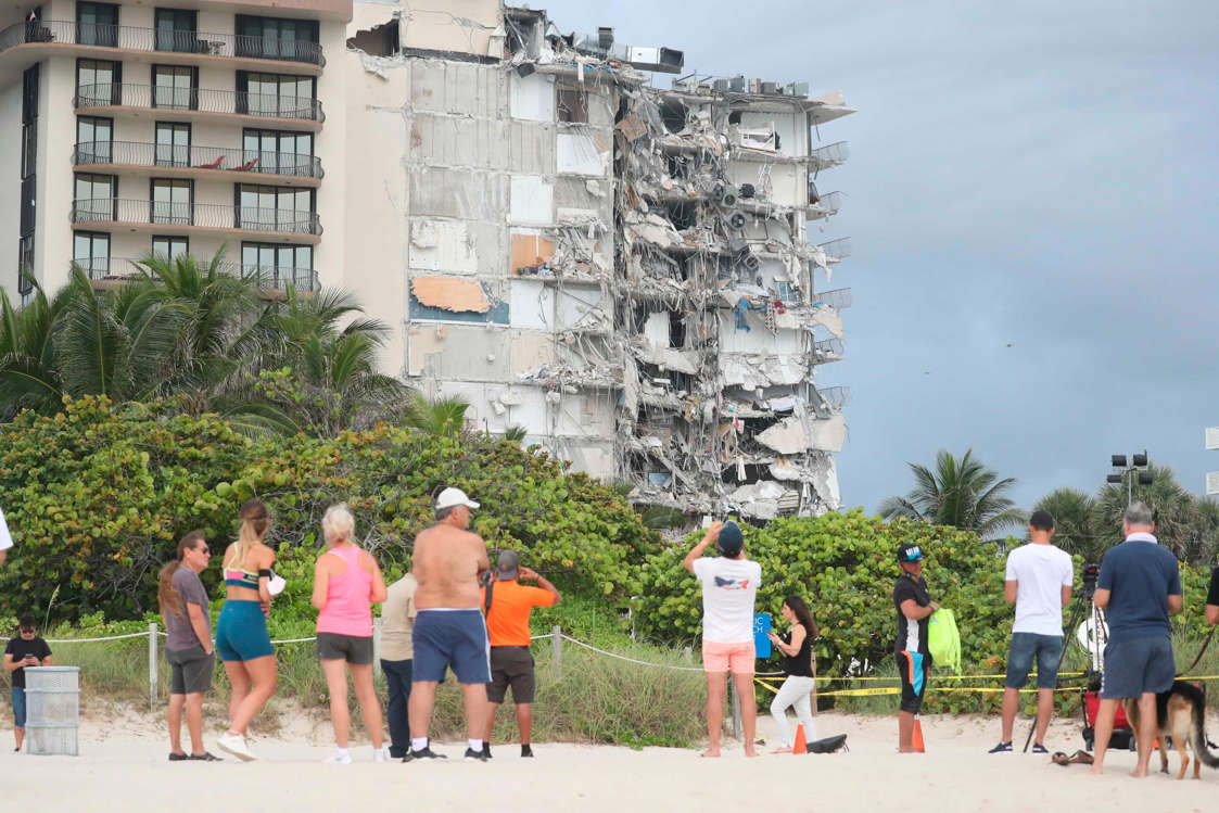 Slide 44 of 58: People look at the damage at the 12-story oceanfront Champlain Towers South Condo that collapsed early Thursday, June 24, 2021 in Surfside, Fla.