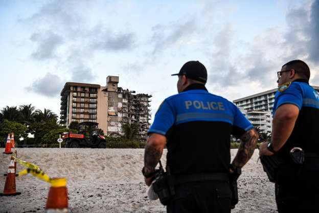 Slide 15 of 34: Police stand guard near a partially collapsed building a partially collapsed building in Surfside north of Miami Beach, on June 24, 2021. The multi-story apartment block in Florida partially collapsed early June 24, sparking a major emergency response. Surfside Mayor Charles Burkett told NBCs Today show: My police chief has told me that we transported two people to the hospital this morning at least and one has died. We treated ten people on the site.