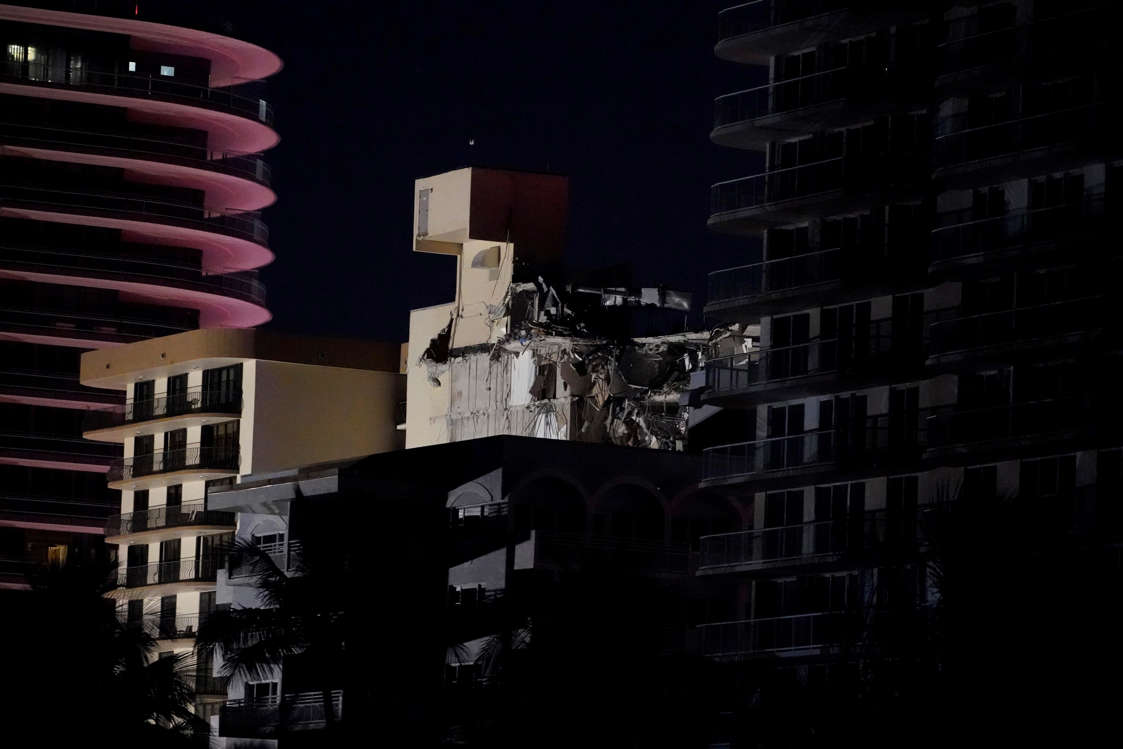 Slide 55 of 58: A partially collapsed building, center, is seen early Thursday, June 24, 2021, in the Surfside area of Miami, Fla.