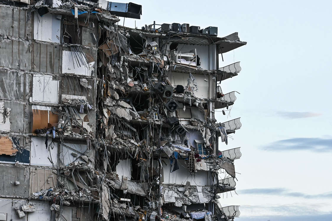 Slide 40 of 58: Rubble hangs from a partially collapsed building in Surfside north of Miami Beach, on June 24, 2021. The multi-story apartment block in Florida partially collapsed early June 24, sparking a major emergency response.