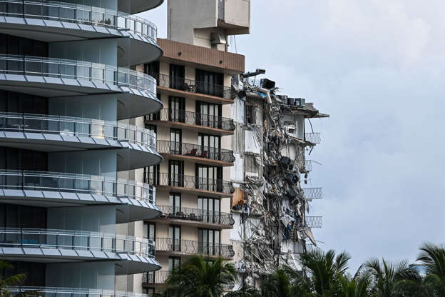 Slide 21 of 34: Rubble hangs from a partially collapsed building in Surfside north of Miami Beach, on June 24, 2021.