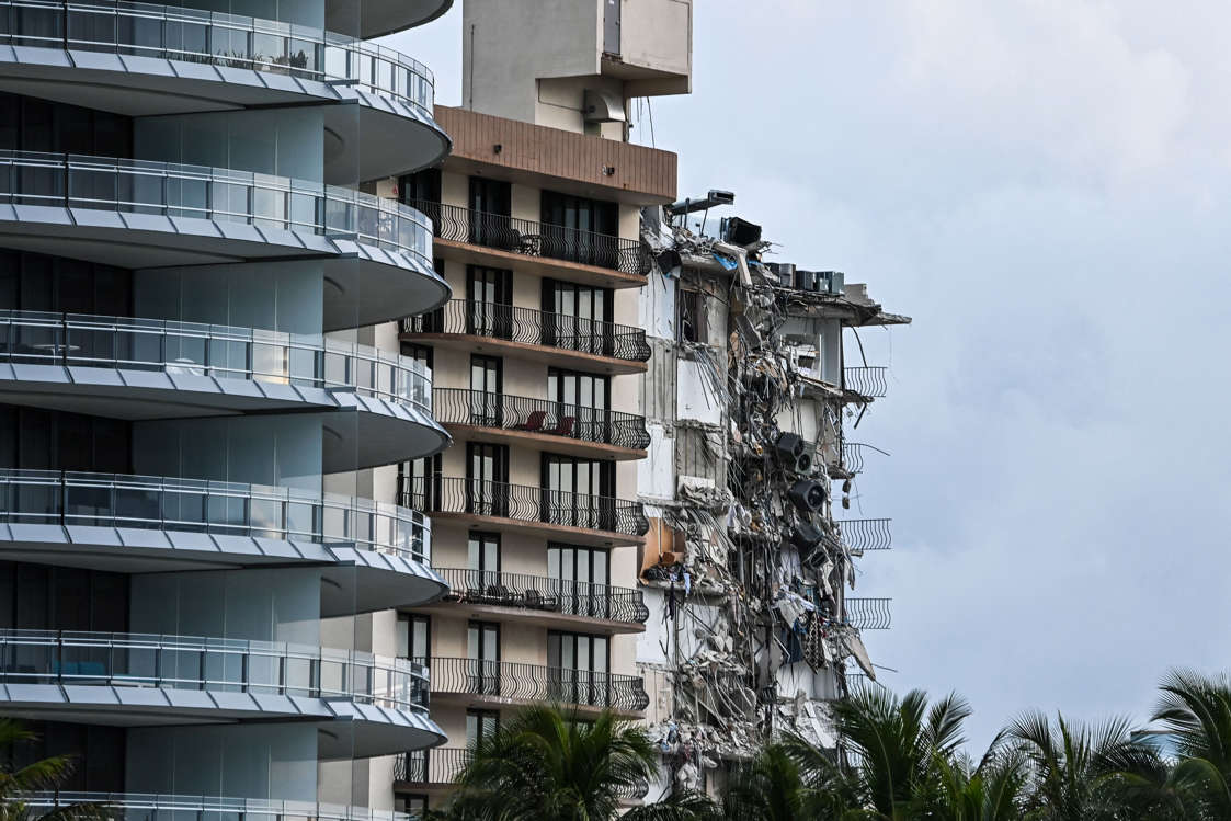 Slide 45 of 58: Rubble hangs from a partially collapsed building in Surfside north of Miami Beach, on June 24, 2021.