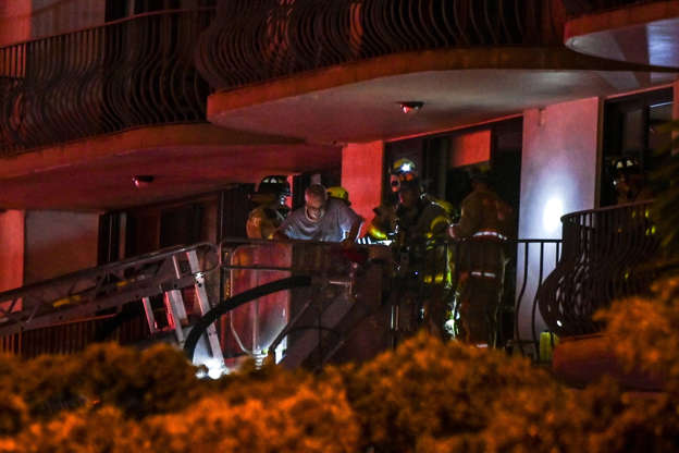 Slide 23 of 34: Fire Rescue workers rescue a resident at a partially collapsed building in Surfside, Fla., on June 24, 2021.A multi-story apartment block in Florida partially collapsed during early June 24, sparking a major emergency response. Online videos showed a large portion of the 12-story building in the town of Surfside -- just north of Miami Beach -- reduced to rubble, with the apartments' interiors exposed.