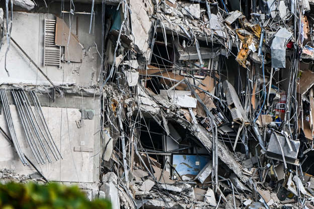Slide 22 of 34: Rubble hangs from a partially collapsed building in Surfside north of Miami Beach, on June 24, 2021.