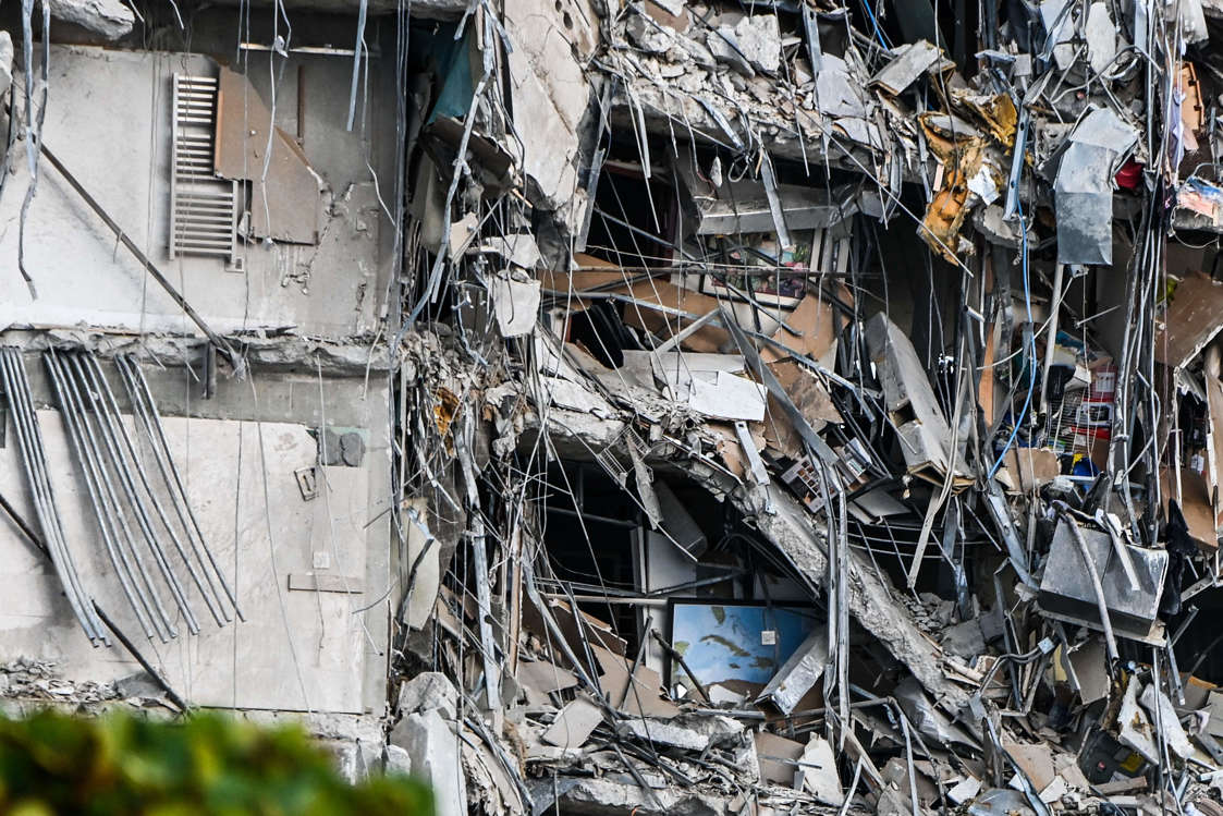 Slide 46 of 58: Rubble hangs from a partially collapsed building in Surfside north of Miami Beach, on June 24, 2021.