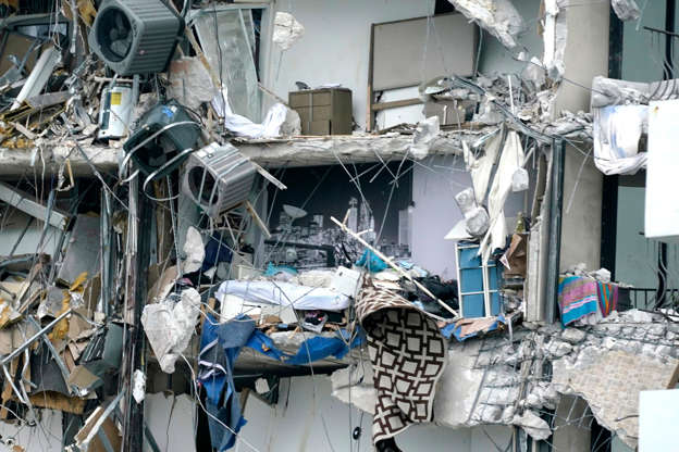 Slide 14 of 34: Household items and debris dangle from a partially collapsed multistory beachfront condo, Thursday, June 24, 2021, in Surfside, Fla.