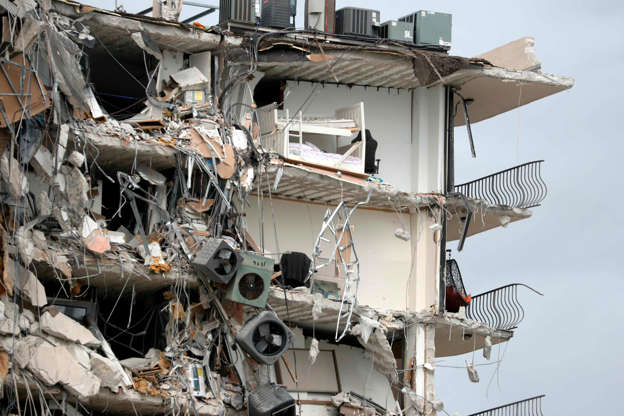 Slide 19 of 34: Items and debris dangle from a section of the oceanfront Champlain Towers South Condo that partially collapsed Thursday, June 24, 2021, in the Surfside area of Miami, Fla.