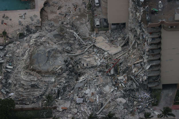 Slide 11 of 34: Search and rescue personnel work in the rubble of the 12-story condo tower that crumbled to the ground during a partially collapse of the building on June 24, 2021 in Surfside, Fla.