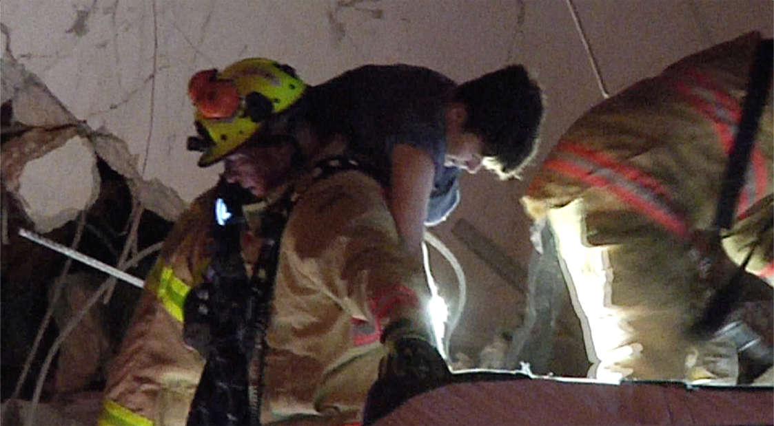 Slide 29 of 58: This photo taken from video provided by ReliableNewsMedia, firefighters rescue a survivor from the rubble of the Champlain Towers South Condo after the multistory building partially collapsed in Surfside, Fla., early Thursday, June 24, 2021.